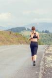 Giovane funzionamento esile della donna sulla strada della montagna Immagine Stock