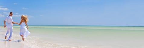 Giovane funzionamento felice delle coppie che si tiene per mano su una spiaggia tropicale fotografie stock