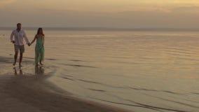 Giovane funzionamento felice delle coppie sulla spiaggia sul tramonto Concetto di amore video d archivio