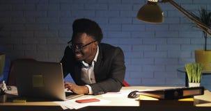 Giovane funzionamento felice di bussinessman all'ufficio di notte Lui che celebra successo, buone notizie sul web video d archivio