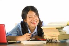 Giovane funzionamento felice sorridente della ragazza cinese asiatica felice e sveglia dello studente e studiare con i texbooks e fotografie stock