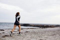 Giovane funzionamento femminile del corridore sulla spiaggia Fotografie Stock
