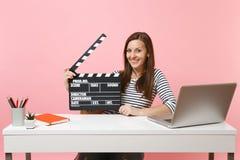 Giovane funzionamento nero classico sorridente di ciac di produzione cinematografica della tenuta della donna sull'attimo di prog fotografia stock