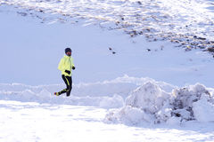 Giovane funzionamento sano dell'uomo di sport in montagne della neve nell'allenamento duro del corridore della traccia nell'inver Fotografia Stock