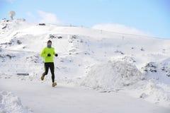 Giovane funzionamento sano dell'uomo di sport in montagne della neve nell'allenamento duro del corridore della traccia nell'inver Immagini Stock
