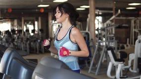 Giovane funzionamento sportivo della ragazza sulla pedana mobile alla palestra forma fisica, sport, salute archivi video