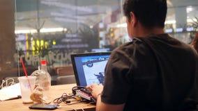 Giovane Gamer adolescente asiatico che gioca il gioco online del tiratore sul computer portatile in caffè 4K Bangkok, Tailandia - archivi video
