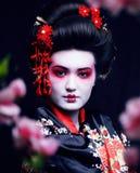 Giovane geisha graziosa in kimono con sakura e decorazione su fondo nero fotografie stock libere da diritti