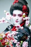 Giovane geisha graziosa in kimono nero fra sakura, primo piano asiatico di ethno fotografia stock