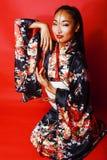 Giovane geisha graziosa su fondo rosso che posa in kimono, orientale immagine stock libera da diritti