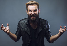Giovane gesturing barbuto attraente dell'uomo dei pantaloni a vita bassa Fotografia Stock