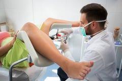 Giovane ginecologo che mette gel sull'attrezzatura al paziente dell'esame immagine stock