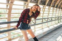 Giovane ginnasta castana attraente del ballerino della via della donna che riposa sul ponte della via all'alba immagine stock