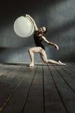 In giovane ginnasta esperta che esegue facendo uso del pallone bianco Immagini Stock Libere da Diritti