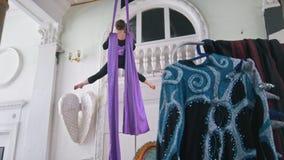 Giovane ginnasta flessibile dell'aria della donna che appende sulla seta aerea video d archivio