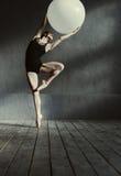Giovane ginnasta ispirata che allunga facendo uso della palla bianca Immagini Stock