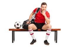 Giovane giocatore di football americano che si siede su un banco fotografie stock
