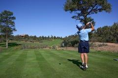Giocatore di golf giovane che colpisce fuori dal T fotografia stock