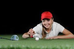 Giovane giocatore di golf femminile sul campo artificiale al mini club di golf Fotografia Stock