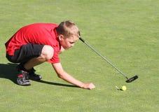 Giovane giocatore di golf maschio che allinea tiro in buca Fotografia Stock Libera da Diritti