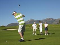 Giovane giocatore di golf maschio che colloca sul tee fuori Immagine Stock Libera da Diritti
