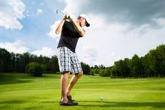 Giovane giocatore di golf sul corso che fa l'oscillazione di golf Immagini Stock