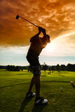 Giovane giocatore di golf sul corso che fa l'oscillazione di golf Fotografia Stock