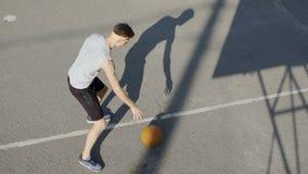 Giovane giocatore di pallacanestro caucasico che gocciola una palla allo stadio, allo sport ed all'hobby archivi video