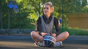 Giovane giocatore di pallacanestro femminile affascinante che sta su dalla terra e che va via, tenendo palla, campo da pallacanes video d archivio