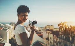 Giovane giornalista femminile sveglio con la macchina da presa d'annata fotografie stock