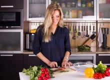Giovane giovane donna graziosa che cucina insalata in cucina Fotografie Stock
