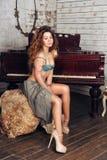 Giovane giovane donna sensuale in biancheria che posa contro il pianoforte a coda Immagine Stock Libera da Diritti