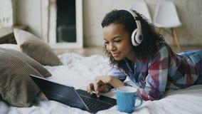 Giovane godere afroamericano riccio della donna ascolta musica sul computer portatile mentre si trova sul letto archivi video