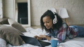 Giovane godere afroamericano riccio della donna ascolta musica sul computer portatile mentre si trova sul letto video d archivio