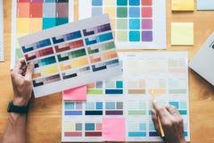 Giovane grafico creativo che per mezzo della tavola dei grafici al choosin immagine stock