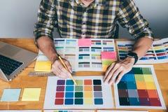 Giovane grafico creativo facendo uso della tavola dei grafici a scegliere il grafico dei campioni del campione di colore per colo fotografie stock