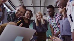 Giovane gruppo che lavora al nuovo progetto Gruppo di gente della corsa mista che sta vicino alla tavola ed alla discussione stock footage
