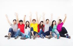 giovane gruppo che si siede insieme contro la parete bianca Fotografia Stock