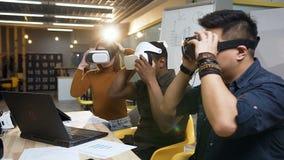 Giovane gruppo di affari che indossa i vetri di realtà virtuale di VR per lavoro con il computer portatile nell'ufficio alla moda archivi video