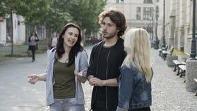 Giovane gruppo di ragazze e di ragazzo degli amici sulla via che reagisce con la scossa che vedono qualche cosa di stupefacente e archivi video