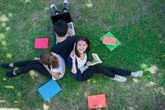 Giovane gruppo di studenti che sorride con le cartelle libro e computer portatile Fotografia Stock