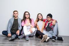 Giovane gruppo di teengers degli studenti degli amici che si siedono sul pavimento Fotografia Stock
