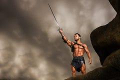 Giovane guerriero su un picco di montagna immagine stock