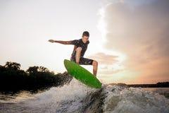 Giovane guida attraente dell'uomo sul wakeboard sui precedenti o fotografie stock