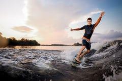 Giovane guida attraente dell'uomo sul wakeboard verde fotografie stock