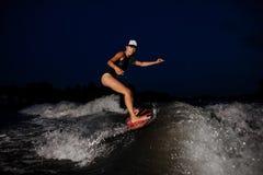 Giovane guida attraente della donna sul wakesurf arancio in vicino fotografia stock libera da diritti