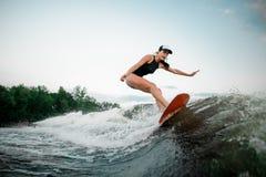 Giovane guida attraente della ragazza sul wakesurf arancio immagine stock libera da diritti