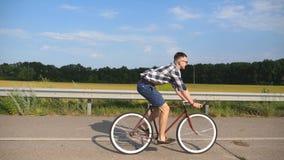 Giovane guida bella dell'uomo alla bicicletta d'annata nella strada campestre Tipo sportivo che cicla alla pista Guida maschio de archivi video