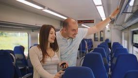 Giovane guida delle coppie in un treno suburbano stock footage