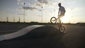 Giovane guida maschio del motociclista sull'orlo della rampa in un addestramento acrobatico al movimento lento di tramonto - stock footage